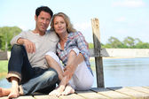 Mid age couple seated on a pontoon near a lake — Stock Photo