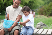 Father and son enjoying fishing party by riverside — Stock Photo