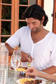 Man opening a bottle of wine at an outdoor lunch — Stock Photo