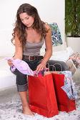 Woman sat looking through shopping bags — Stock Photo