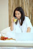 Mulher na cama com café da manhã e seu laptop — Foto Stock