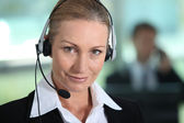 Woman smiling with headset — Stock Photo