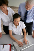 Business couple overseeing a woman talking through a headset — Stock Photo