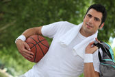Angled shot of man with basketball and kit bag — Stock Photo