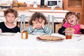 Three children eating crepes — Stock Photo