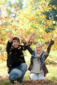 Man and woman throwing leaves — Stock Photo