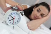 A woman stopping an alarm clock — Stock Photo