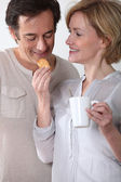 Woman with cup of coffee feeding her partner a biscuit — Stock Photo