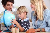 Happy family looking terrestrial globe — Stok fotoğraf