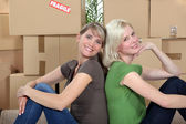 Twosome of young girls moving in together sitting back-to-back — Stock Photo