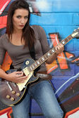 Female guitarist stood by painted wall — Stock Photo