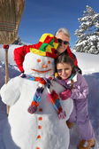 Father and daughter building snowman — Stock Photo
