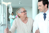 Male doctor helping elderly patient — Stock Photo