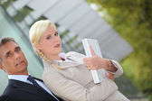 Business couple standing outside with a laptop — Stock Photo