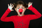 Little girl surprised with a clown nose — Stock Photo