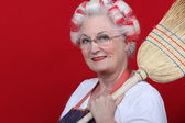 An old lady with hairroller on and a broom. — Stock Photo