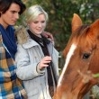 Young couple petting horse — Stock Photo