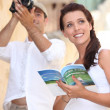 Stock Photo: Tourists with camerand travel guide