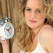 Woman holding alarm clock — Stock Photo