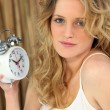 Woman holding alarm clock — Stockfoto