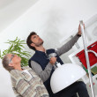 Young man putting up a light for an elderly woman — Stock Photo #8062856