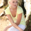 Platinum blonde woman near trees - Stock Photo