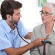 Medic listening to a senior woman's chest — Stock Photo #8062969