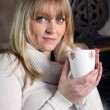 Young woman with a hot drink at home — Stock Photo