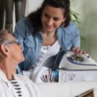 A young woman ironing and talking to an older woman — Stock Photo