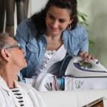 Молодая женщина, Гладильные системы и говорить с пожилой женщиной — Стоковое фото
