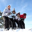 Four friends skiing together on holiday — Stock Photo #8063281
