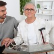 Elderly person looking at photos with son — Foto Stock