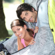 Stock Photo: Young couple sticking their heads out of tent door
