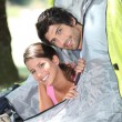 Foto Stock: Young couple sticking their heads out of tent door