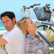 Couple with bikes on the beach — Stock Photo #8063549