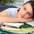 Young brunette lying flat near  PC with books and files — Foto Stock