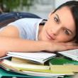 Young brunette lying flat near PC with books and files — Stock Photo