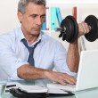 Royalty-Free Stock Photo: A mature businessman lifting weights in his office.