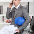 An annoyed architect talking on the phone - Stock Photo