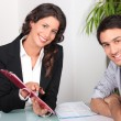 Woman showing man where to sign - Foto Stock
