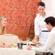 Waitress serving young couple in restaurant — Stockfoto #8065281