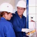 un elettricista insegna come utilizzare un amperometro — Foto Stock