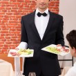 Waiter delivering meals to table - Stock Photo