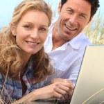 Couple smiling on laptop. — Stock Photo