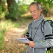 Sixty years old man taking notes on a forest trail — Stock Photo