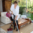 Stock Photo: Young womvacuuming