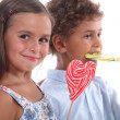 Two skittish kids with lollypops - Stock Photo