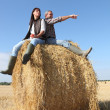 Stock Photo: Farmer and wife sat on hay roll