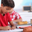 Stock Photo: Little boy focusing on his work in classroom