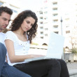 Couple using laptop computer outdoors - Stock Photo